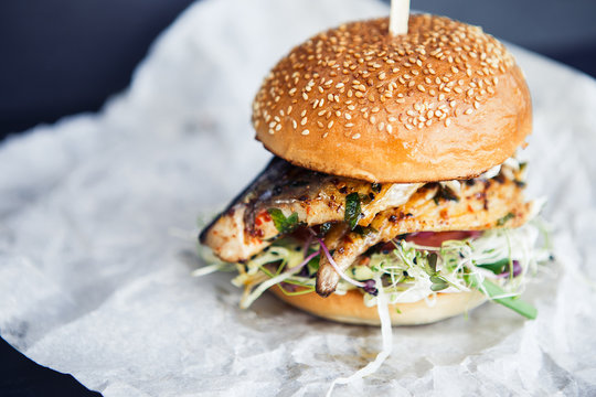 Tasty fresh street food vegan or vegetarian fish burger on the butter-paper on the black background. Sweet sesame bun with fish, micro-green, tomato and black pepper. American classic food concept.