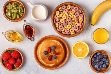 Breakfast with colorful cereal rings, pancakes, fruit, milk, juice.