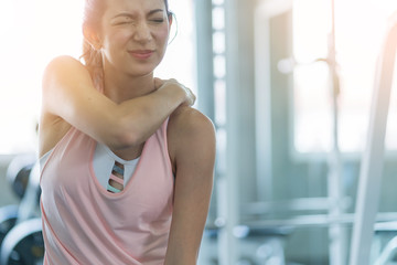 woman get accident between workout in gym shoulder pain and hurt with wrong posture  exercise