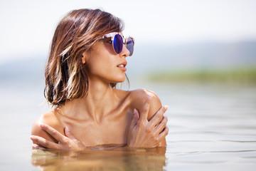 girl posing in water near a beach