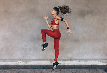 Sportswoman jumping and stretching Wall mural