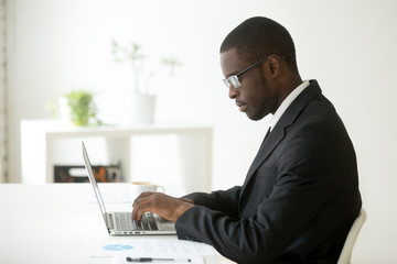 Concentrated self-employed African American manager in glasses and formal wear working at laptop, typing company financial report or reading business email at workplace. Concept of focus, hardworking