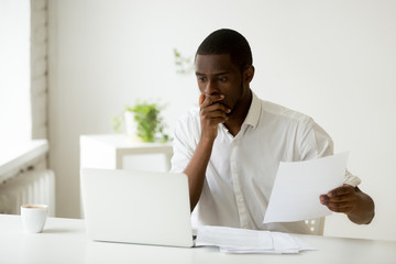 Frightened worried African American worker made a mistake desperately looking at laptop screen, something bad happened, person having problems with report data statistics, witnessing operation failure