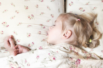 Sleeping little girl with arms protruding from under the blanket