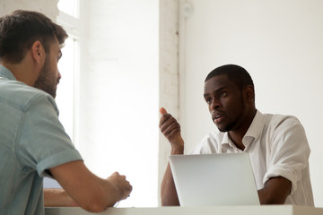 Serious African American worker talking to Caucasian colleague, discussing work issues, negotiating about shared business project during corporate company meeting in office. Multiethnic collaboration