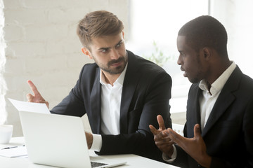 Multiethnic office workers disputing on contract issues, African American explaining his thoughts to Caucasian colleague. Businessmen arguing and disagreeing about paperwork documentation