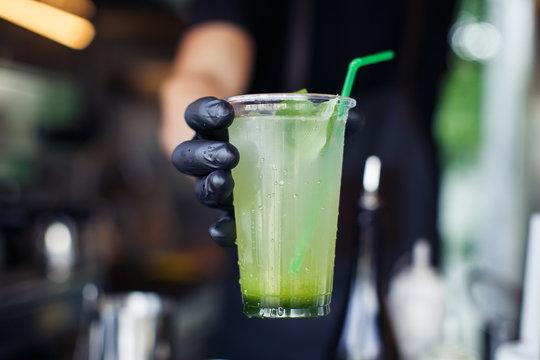 Handing cucumber lemonade in plastic cup from foodtrack