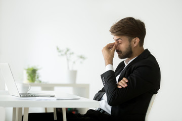 Exhausted businessman feeling tired after long hours working at laptop, massaging nose bridge, suffering from eye strain, trying to relieve pain. Concept of overwork, fatigue at workplace