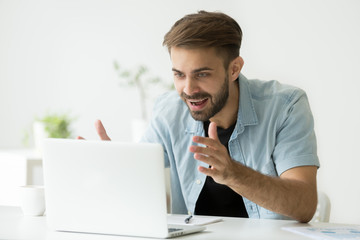 Excited casual happy male worker looking at laptop screen, gaining profit, satisfied with successful investment, winning lot of money in lottery, getting promoted. Concept of reward, luck, achievement