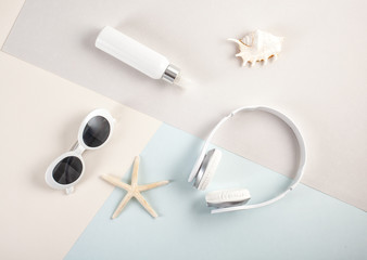 Top view to essential summer accessories sunglasses, earphones and sunscreen