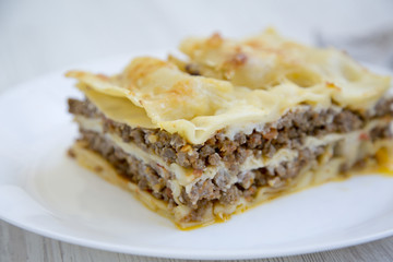 Italian beef lasagne on a white round plate, white wooden background. Side view.