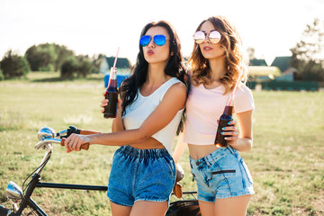 Two beautiful sexy girls, hipsters, modern style, ride a bike and roller skates, and drink soda through the straws, Summer time, fun, sunset in nature