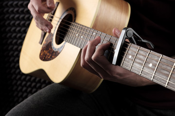 Close photo of the guitar playing male hands.