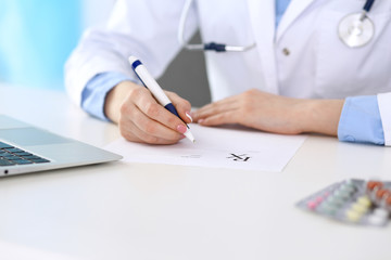 Female doctor filling up prescription form while sitting at the desk in hospital closeup.  Healthcare, insurance and excellent service in medicine concept