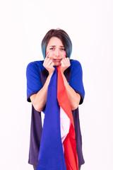 Portrait d'une jeune supportrice de l'équipe de France de football, le drapeau national dans ses mains