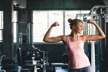Woman strong posing  at sport gym weight training with happy smile feeling, gym workout concept