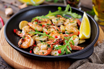 Prawns Shrimps roasted in garlic butter with lemon and parsley on wooden background. Healthy food.