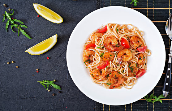 Pasta spaghetti with shrimps, tomato and parsley. Healthy meal. Italian food. Top view. Flat lay
