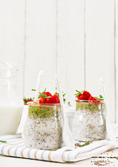 Detox and healthy superfoods breakfast in jar. Vegan coconut milk chia seeds pudding with strawberries and kiwi.