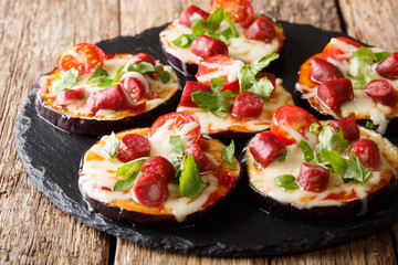 Delicious aubergines with mozzarella cheese, tomatoes, sausages and sauce close-up on a slate board. horizontal