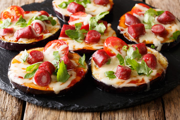 Mini pizza from eggplants with mozzarella, tomatoes, sausages and greens close-up. horizontal