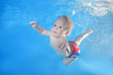 little boy dives underwater in the pool