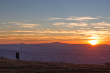 A couple looking at sunset from the top of a mountain
