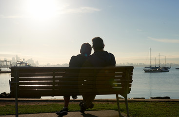 A silhouette of a couple sitting on a bench by the waters edge enjoying the sun in their face and vista of water and boats