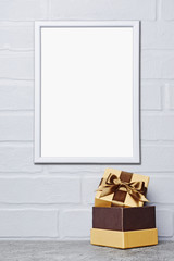 Mock-up of white frame with copy space for poster and golden classic gift box with brown satin bow