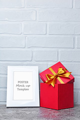Mock-up of white frame with copy space for poster and red classic gift box with golden satin bow