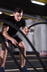 athlete man doing battle ropes cross fitness exercise
