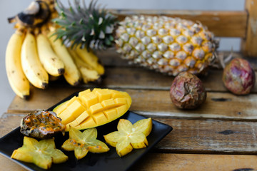 Close up yellow mango with carambola on plate near pine-apple and bananas on wooden table. Concept of tasty food and tropical fruits.
