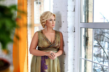 Charming blonde woman in colorful dress, standing near window