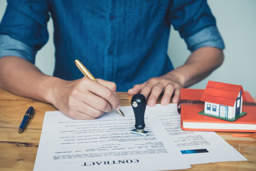 Rubber stamp put on the table between real estate agent holding house to his client after signing contract,concept for real estate,insurance with house, moving home or renting property
