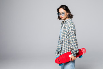 Pretty young skater girl holding skateboard isolated on gray background