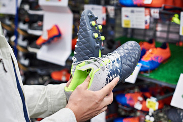 Hands of man with football boots in sport store