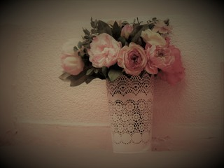Bouquet of flowers with roses, in a vase with a paper cuff, arranged in front of a pink environment, the picture is exposed and developed in the style of a paper photo from the 1950s.