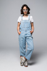 Full height attractive beautiful woman wearing in overalls with sunglasses and smiling at camera with happy and joyful isolated on gray background