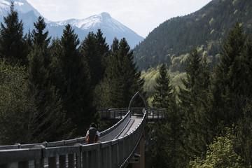 Young adult male walking over a bridge at a tree top walkway in the german alps