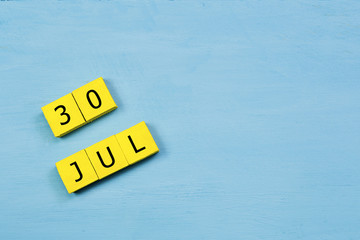 JUL 30, yellow cube calendar on blue wooden surface with copy space