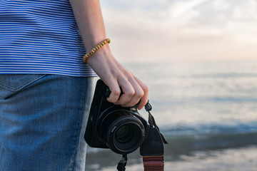 woman's hand holding the camera against the sea.close up