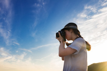 girl photographer takes a picture against the blue sky and sunset, the bottom view