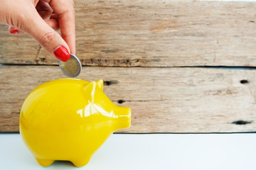 Woman hand inserting coin in a yellow piggy bank, savings for future concept
