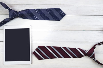 Happy Father's Day inscription with colorful tie and digital tablet on wooden background floor backround.