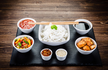 Roasted meat, rice noodles and vegetables on wooden background