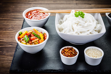 Rice noodles and vegetables on wooden background