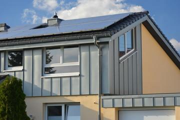 Dunkles Ziegeldach mit Metall-Stehfalz-Zinkblech Randabschluss- und Fassadenverkleidung eines modernen Gebäudes mit Solaranlage, Regenrinne, Regenfallrohr, Wasserfangkasten und Schneefang