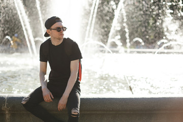 Stylish man at the fountain in hot summer day. He wearing in black jeans, black T-shirt, black cap with riund sunglasses