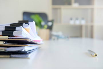 Stack of paper files and pen business equipment on office table.