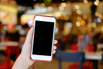 Hands holding smartphone empty display mockup mobile with cafe blur background.